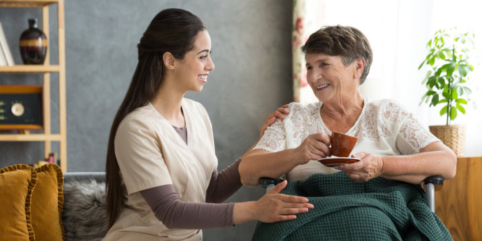 Young nurse serving coffee to senior woman